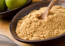 Brown Sugar. A bowl of sifted brown sugar with apples and wooden spoon stock photography