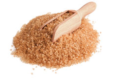 Brown sugar. Heap of brown sugar and wooden scoop on white background Royalty Free Stock Photos