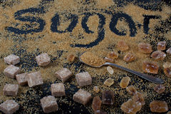 Brown sugar on black background crystal and cubes. With spoon royalty free stock images