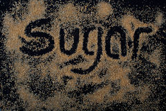 Brown sugar on black background. Crystal with note royalty free stock photo