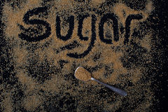 Brown sugar on black background. Crystal with spoon stock images