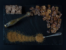 Brown sugar on black background cubes and crystal. With spoon and nippers stock image