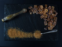 Brown sugar on black background cubes and crystal. With spoon and nippers royalty free stock images