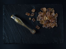 Brown sugar on black background cubes nippers. Brown sugar on black background cubes with nippers stock image