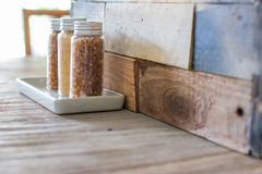 Brown sugar in the bottles on wooden table Royalty Free Stock Photos