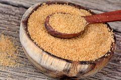 Brown sugar in a bowl and spoon on table Stock Photography