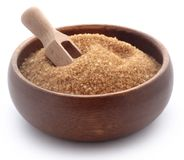 Brown sugar. In bowl with wooden scoop over white background Stock Photos