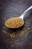 Brown sugar closeup. In a spoon on a dark vintage stone surface Royalty Free Stock Images