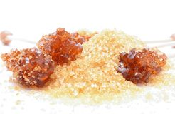 Brown sugar crystal on wooden stick and brown granulated sugar Royalty Free Stock Photos