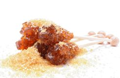Brown sugar crystal on wooden stick and brown granulated sugar Royalty Free Stock Image