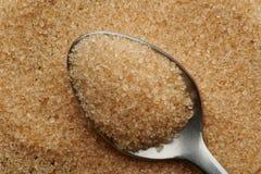 Brown sugar crystals in metal spoon. Macro close up view stock photo