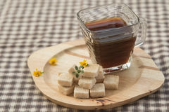 Brown sugar cube and black coffee Royalty Free Stock Image