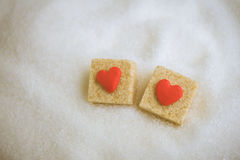 Brown sugar cube decorated  by little red heart  on  white sugar Royalty Free Stock Images