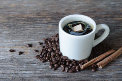 Brown sugar cube falling  into hot coffee mug with coffee beans Royalty Free Stock Photography