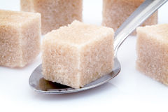 Brown sugar cube and spoon Stock Photos