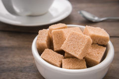 Brown sugar cubes in bowl and coffee cup Royalty Free Stock Photography
