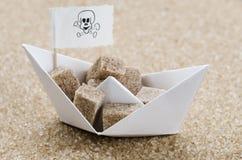Brown sugar cubes in a brouw sugar sea. Brown sugar cubes in a brown sugar sea in a paper boat Stock Photo