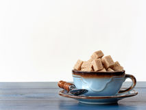 Brown sugar cubes in cup. Organic brown sugar cubes in blue ceramic cup on wood with white background Royalty Free Stock Images