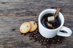 Brown sugar cubes falling  into hot coffee mug with coffee beans Royalty Free Stock Photo