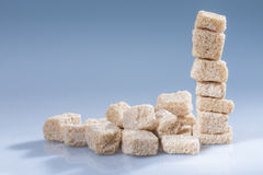 Brown sugar cubes - horizontal. Vertical stack of brown sugar cubes on blue. Horizontal royalty free stock photos