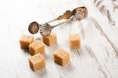 Brown sugar cubes and metal sugat tongs Stock Image