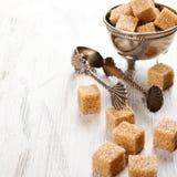 Brown sugar cubes and metal sugat tongs Royalty Free Stock Images