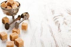 Brown sugar cubes and metal sugat tongs Stock Images