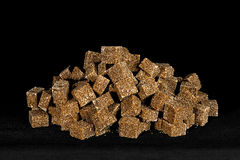 Brown sugar cubes piled. On a black background Stock Photography