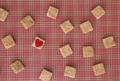 Brown sugar cubes with a red heart on one of them. Top view. Diet unhealty sweet addiction concept Royalty Free Stock Image
