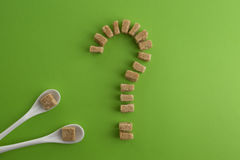 Brown sugar cubes shaped as a question mark on greenery background. Top view. Diet unhealty sweet addiction concept Royalty Free Stock Photos