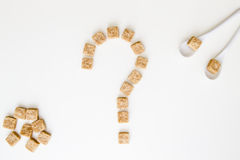 Brown sugar cubes shaped as a question mark on white background. Top view. Diet unhealty sweet addiction concept Stock Photography