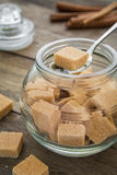Brown sugar cubes in spoon on jar Stock Images