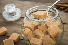 Brown sugar cubes in spoon on jar Stock Photo