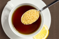Brown sugar and a cup of tea Stock Photography