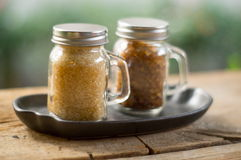 Brown sugar in glass bottle. On wooden table Stock Images