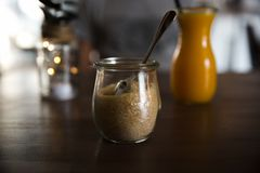 Brown sugar in glass jar and orange fresh juice on wooden table royalty free stock photo