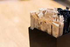 Brown sugar sachets in black box on a counter at a cafe.  stock images