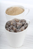 Brown sugar in white cups Stock Photos