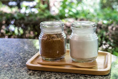 Brown sugar. And white sugar in small glass bottle Stock Photography
