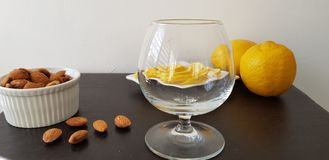 Brown table with brande glass, roasted almonds and lemons slices stock photo