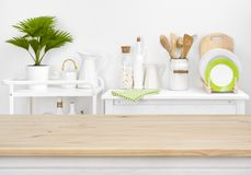 Brown tabletop with copyspace over blurred kitchen shelves with utensils stock photos