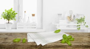 Brown tabletop with towel and leaves on defocused kitchen background.  royalty free stock photography