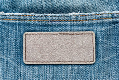 Brown tag on blue jeans texture Stock Image