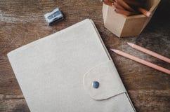 Brown-Tagebuchabdeckung mit Bleistiften und Bleistiftspitzer auf hölzernem Ba Stockfotografie
