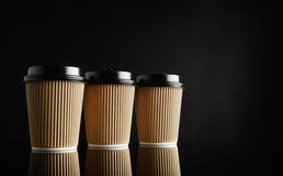 Brown takeaway coffee cup mockups. Three identical light brown cardboard takeaway coffee cups with black lids in a row on reflective black table against black Stock Image