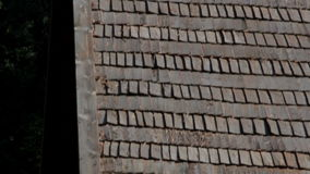 The brown tar oiled wooden shingle shake roof of a big lath Fenced log House stock video