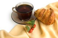 Brown-Tasse Tee und Hörnchen Stockbild