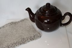 Brown Teapot andd Rustic Wool Yarn Knit Hotpad stock image