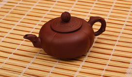 Brown teapot on the bamboo table-cloth Royalty Free Stock Images
