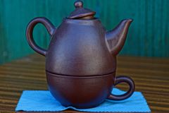 Brown teapot and a cup on a blue tablecloth on a table. Old ceramic brown teapot and a cup on a blue tablecloth on a table Stock Photos